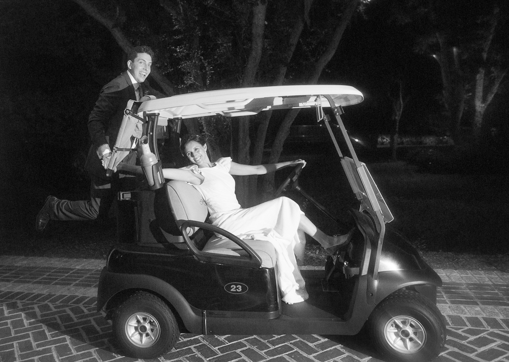 Bride's gown by Delphine Manivet. Menswear by SuitSupply. Getaway golf cart from River Course at Kiawah Island Club. Photograph by Captured by Kate at River Course at Kiawah Island Club.