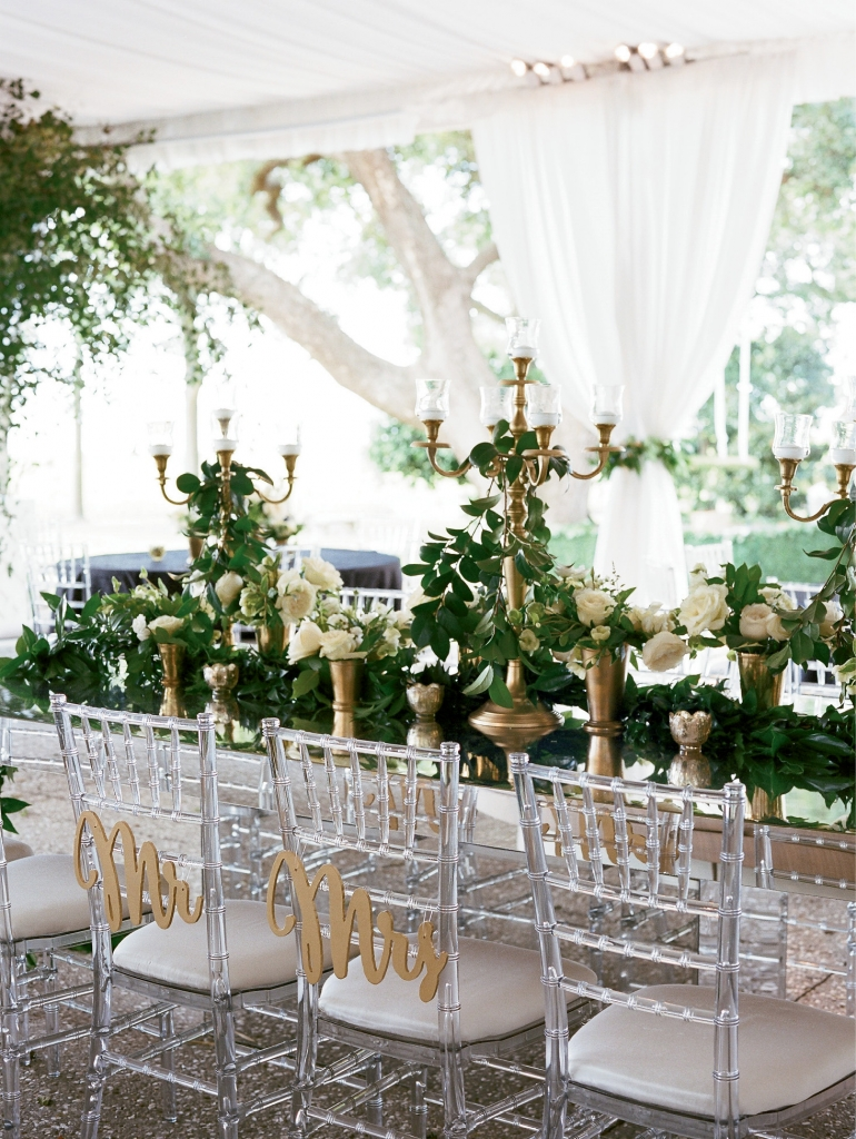 Crystal chandeliers, ghost chiavari chairs, candle-lit mirrored tables, and lush garlands, white orchids and roses made for an opulent, yet intimate dining experience.   <i>Photograph by Gayle Brooker</i>