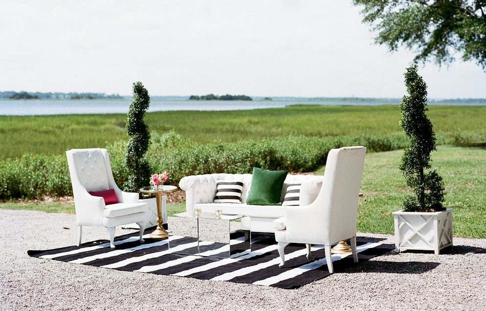 Lounge areas were defined by black and white striped rugs, and outfitted in white leather seating with emerald-hued velvet pillows and mirrored side tables.  <i>Photograph by Gayle Brooker</i>