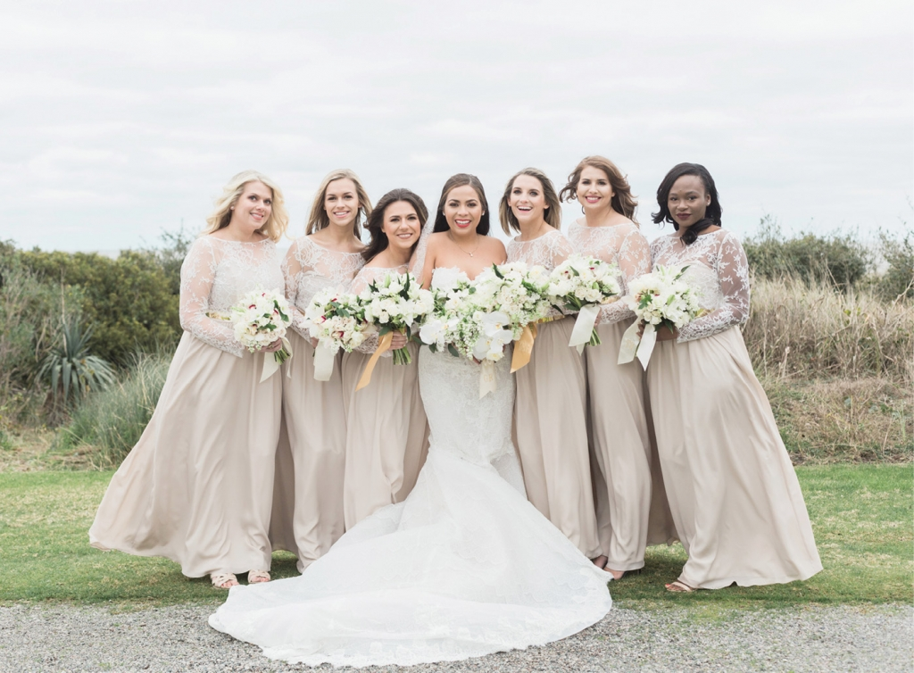 Fearing that white was too trendy for bridesmaids' dresses, Gaby picked metallic gold sashes and sheer, lace bodices made for a striking contrast. The maids of honor's bouquets were tied in gold-hued ribbon.  <i>Photograph by Corbin Gurkin</i>