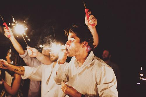 LIGHT UP THE SKY: Wedding guests illuminated the bride and groom's departure with a sparkler sendoff. One crafty guest used his sparkler to light up a celebratory cigar.