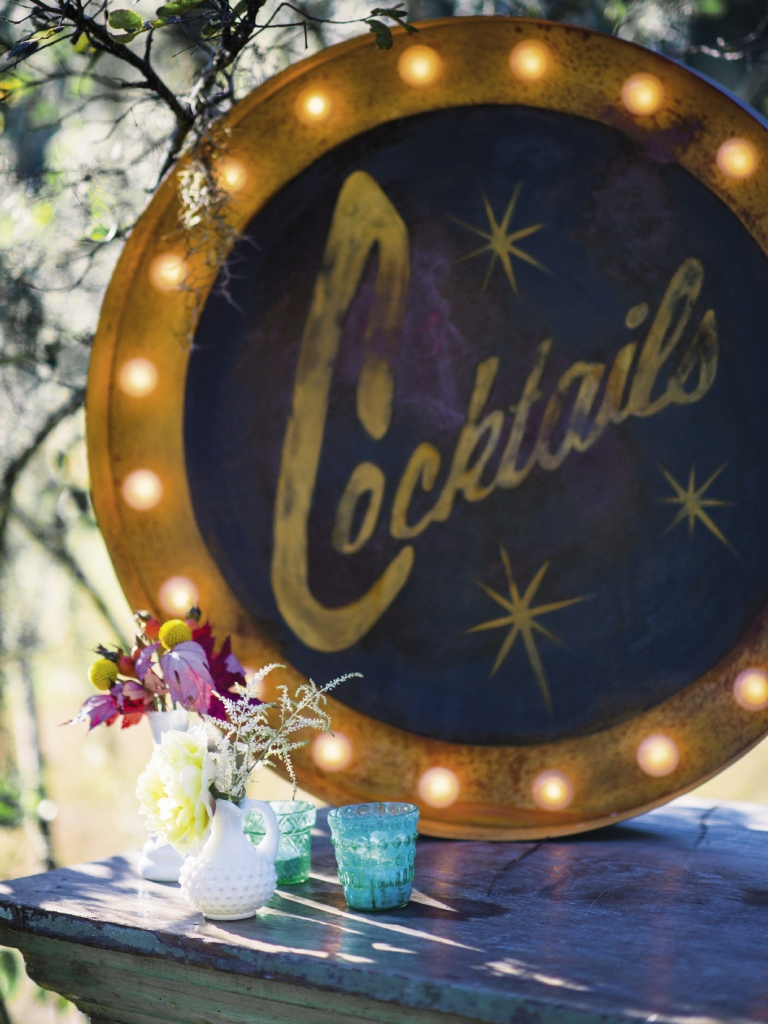 "DRINKS ON US: A 1920s ""Cocktails"" sign from Ooh! Events cast a glamorous glow over the zinc-topped bar."