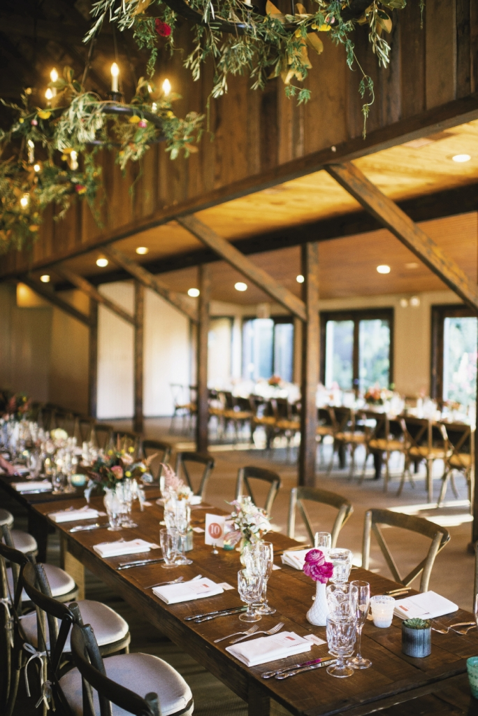 "GARDEN PARTY:  Magnolia and olive branches, craspedia, and ranunculus were woven into the chandeliers to transform the dining hall space into an enchanted garden. Later that night, Lindsay says she and Brian ""felt like we were having an intimate meal with 120 of our loved ones."""