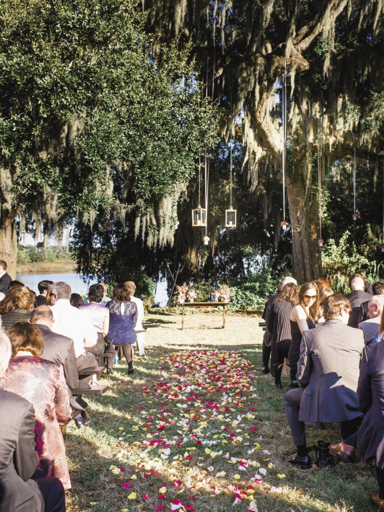 """HERE COMES THE SUN: The two swapped """"I dos"""" at a farm table bathed in sunlight overlooking the Ashley River."""