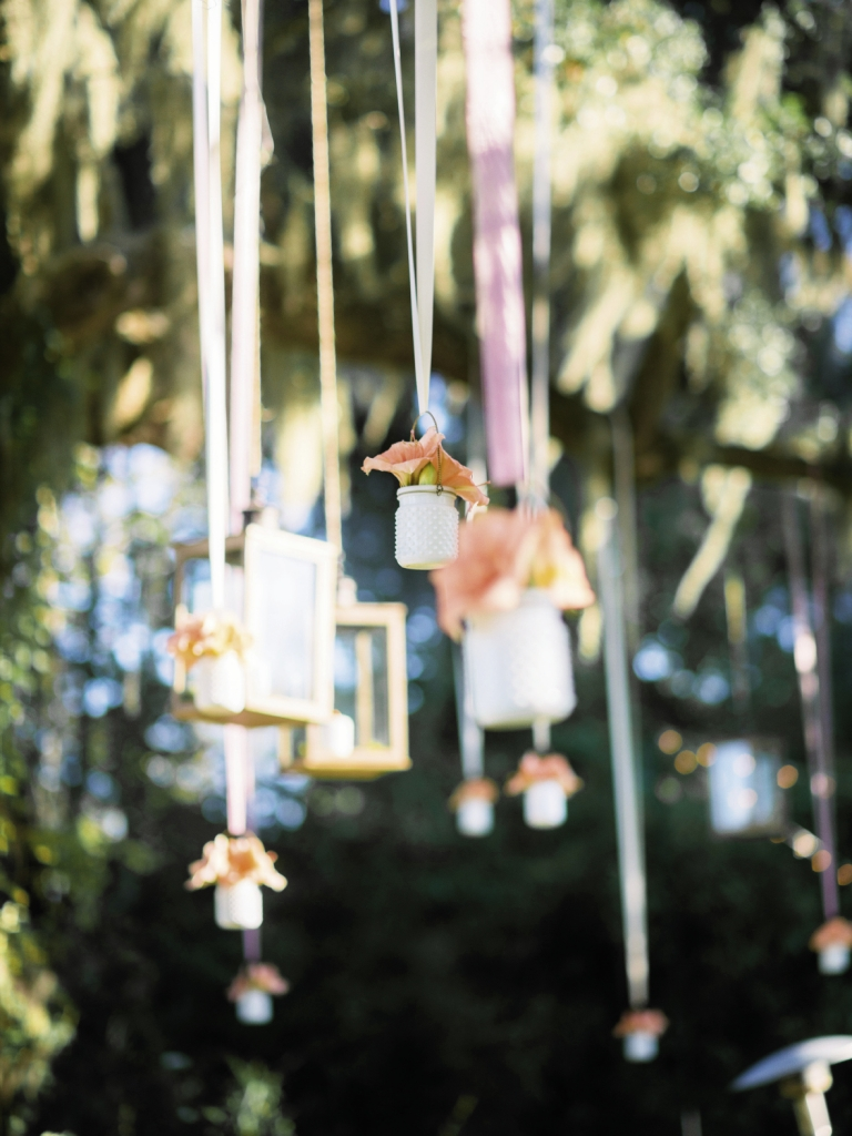 FAIRY TALE: To frame the couple's big moment, Whitney Randall of Branch Design Studio tucked coral amaryllis blooms into opaque milk glass jars and hung them among glass lanterns in the live oak above the altar.