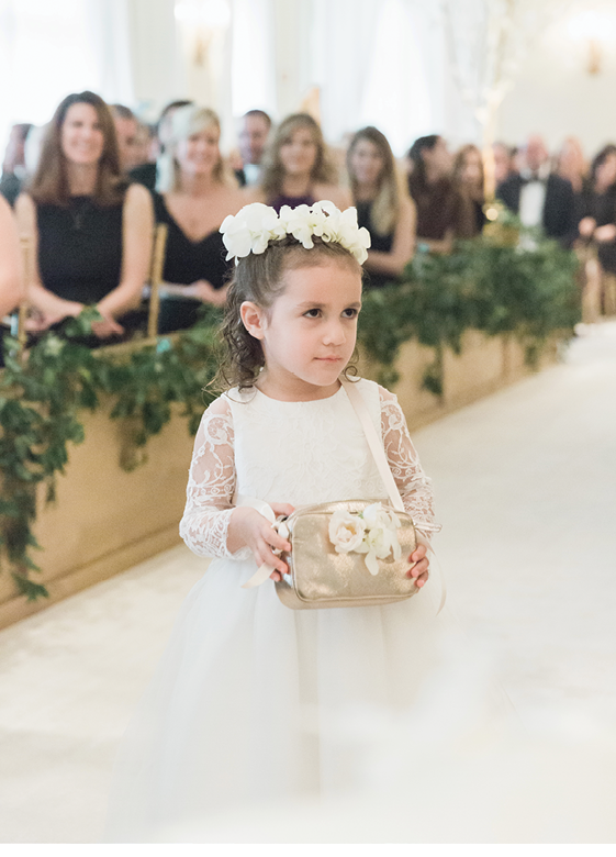Flower girls, like three-year-old Dahlia, wore dresses that harkened those of the bridesmaids' and carried rose petals in gold cross-body bags.   <i>Photograph by Corbin Gurkin</i>