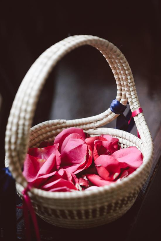 IN PIECES: The flower girls carried deep pink rose petals in sweetgrass baskets. To reiterate the palette, navy and pink ribbons were tied to the basket handles.