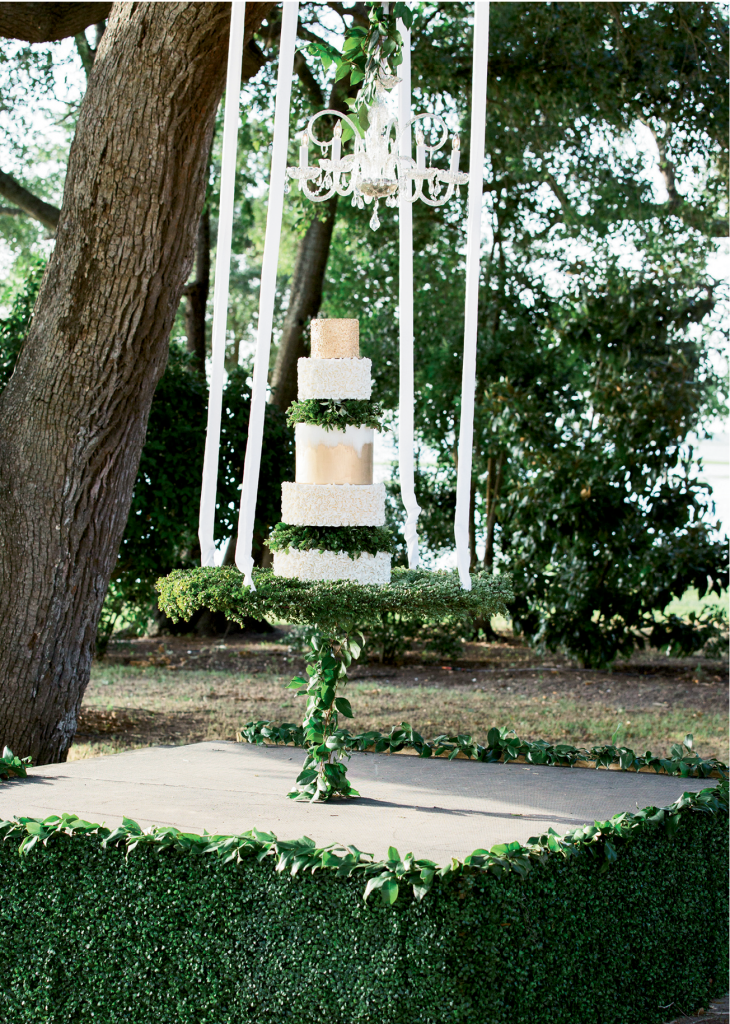 To prevent the cake from swinging during the cutting, Lauren's team ran a greenery-covered cable from the stage to the platform, thus securing the dessert by Patrick Properties pastry chef Jessica Grossman.   <i>Photograph by Gayle Brooker</i>
