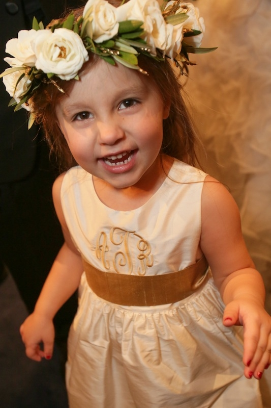 Flower girl dress by Coren Moore from Bella Bridesmaids. Floral headpiece by Charleston Stems. Image by The Connellys.