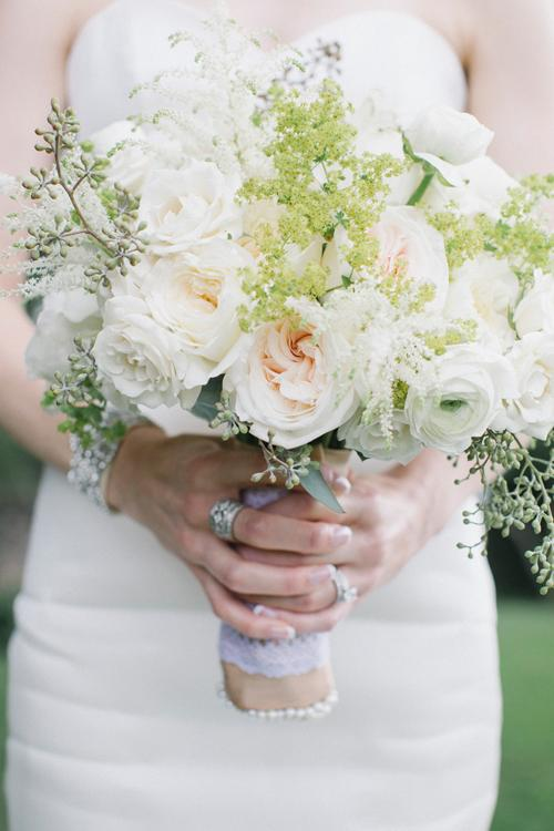 BLOOMING BEAUTY: Branch Design Studio married pale pink garden roses with white ranunculus and white spirea, dotted with stems of greenery, for Abby's bouquet.
