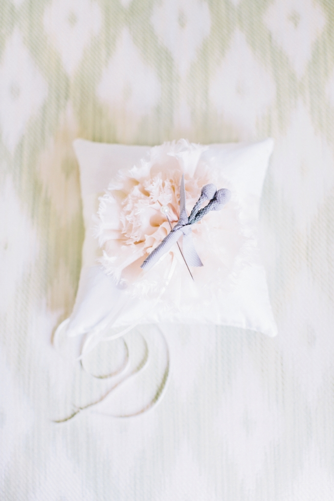 SOFT SPOT: Kim Morgan made this satin ring bearer pillow, while planner Tara Guérard crafted a silver brunia boutonniere tied off with grey grosgrain.