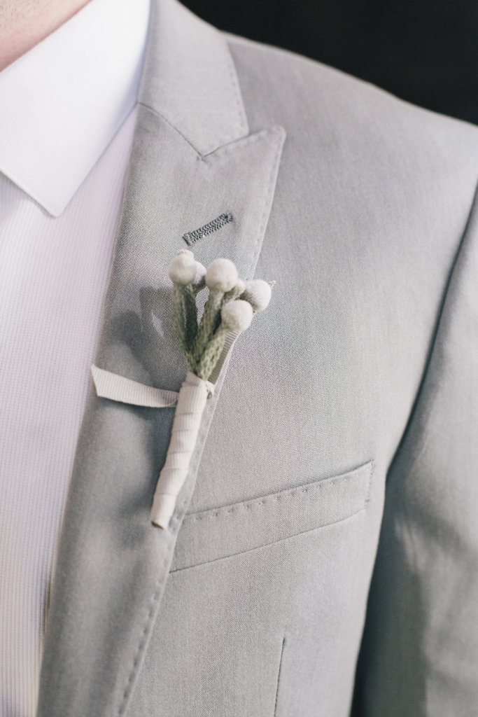 SOFT TOUCH: Tara Guérard pinned understated boutonnieres wrapped in white ribbon on the lapels of groomsmen's light grey suits.