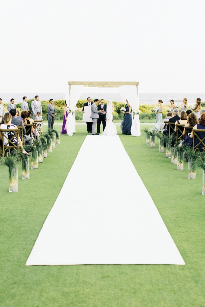 WILD IDEAS: The Sanctuary Hotel's immaculate lawn made the pearl-white aisle runner a pristine  possibility. Bear grass bedded in sand-filled glass  cylinders lined the aisle. The rustling blades danced in the wind and harkened the nearby dune vegetation.
