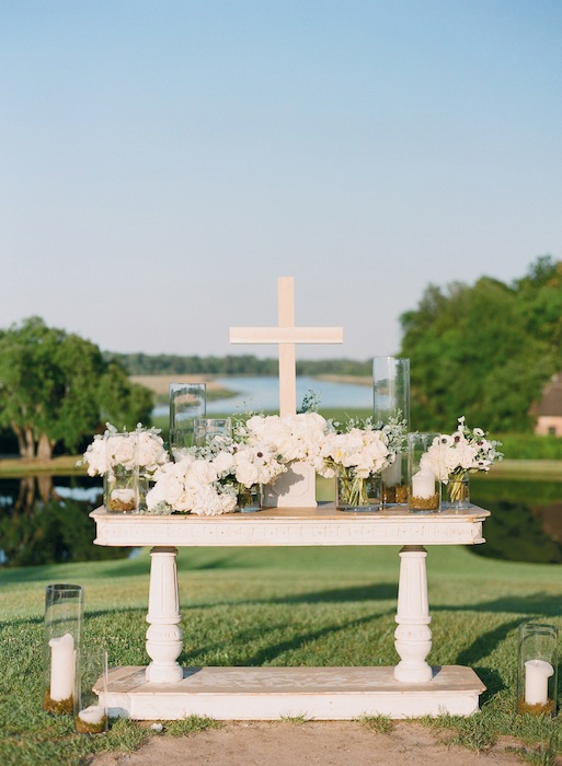 WHITE WEDDING: Dusty miller, lamb's ears, lilac, peonies, ranunculus, spray roses, tetra anemones, and Queen Anne's Lace dressed an altar from Snyder Events. Colors were kept simple so as not to detract from the natural beauty.