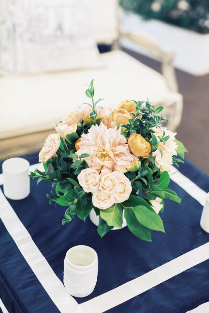 Greens dominated the setting, but a handful of blooms popped up in arrangements starring cheery, warming coral hues.