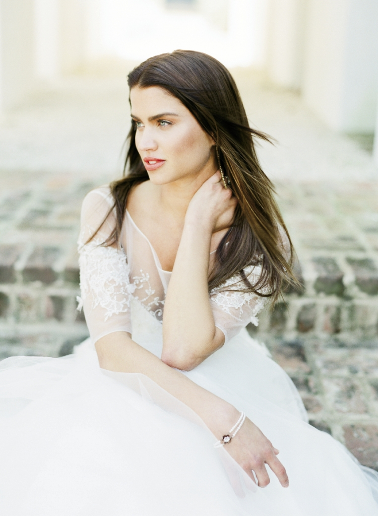 """PORTRAIT OF A LADY: Anne Barge's  """"Serenade"""" A-line tulle and Chantilly lace gown with illusion bateau neckline and three-quarter length sleeves from White on Daniel Island. Gold and crystal chain earrings from Out of Hand. Heirloom pearl, silver, and crystal bracelet from Fabulous Frocks. Platinum ring with 1.51 ct. old European-cut diamond from Croghan's Jewel Box."""
