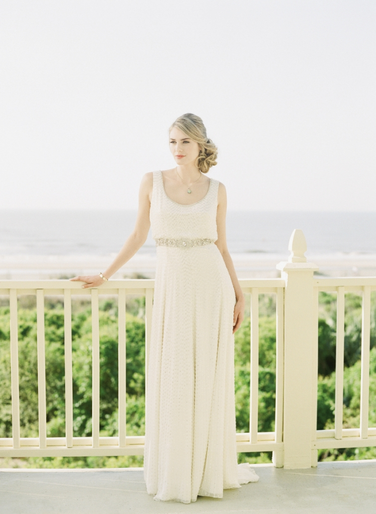 "Oceanfront Oasis: Jenny Packham's ""Kathleen"" scoop-neck gown with beading from White on Daniel Island. Phillips House's 14K gold and diamond bangle from Croghan's Jewel Box. CGC  Collections' 24K  gold-plated necklace with opal pendant  from Finicky Filly."