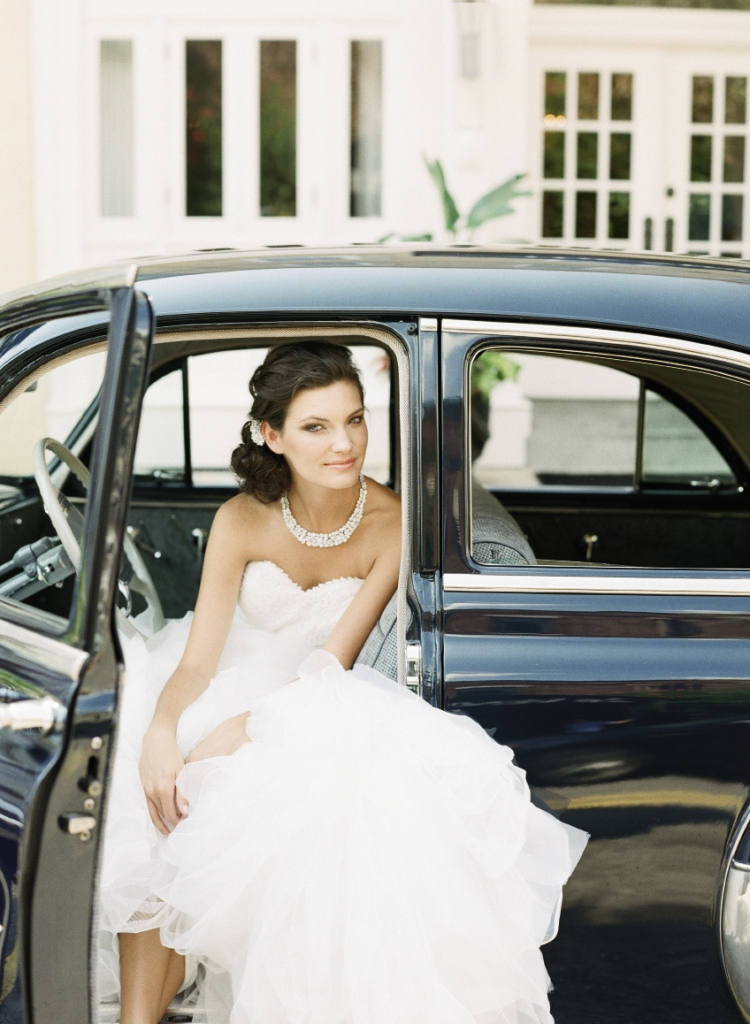 "Pronovias' ""Beca"" mermaid-style gown with embroidered sweetheart bodice and tulle and organza ruffled skirt from Gown Boutique of Charleston. Crystal hair clip from Jean's Bridal. Mariell's rhinestone  collar necklace from White on Daniel Island. 1950 Chevrolet Bel Air Deluxe car from Lowcountry Valet & Shuttle Co. Image by Corbin Gurkin, photographed at The Vendue."