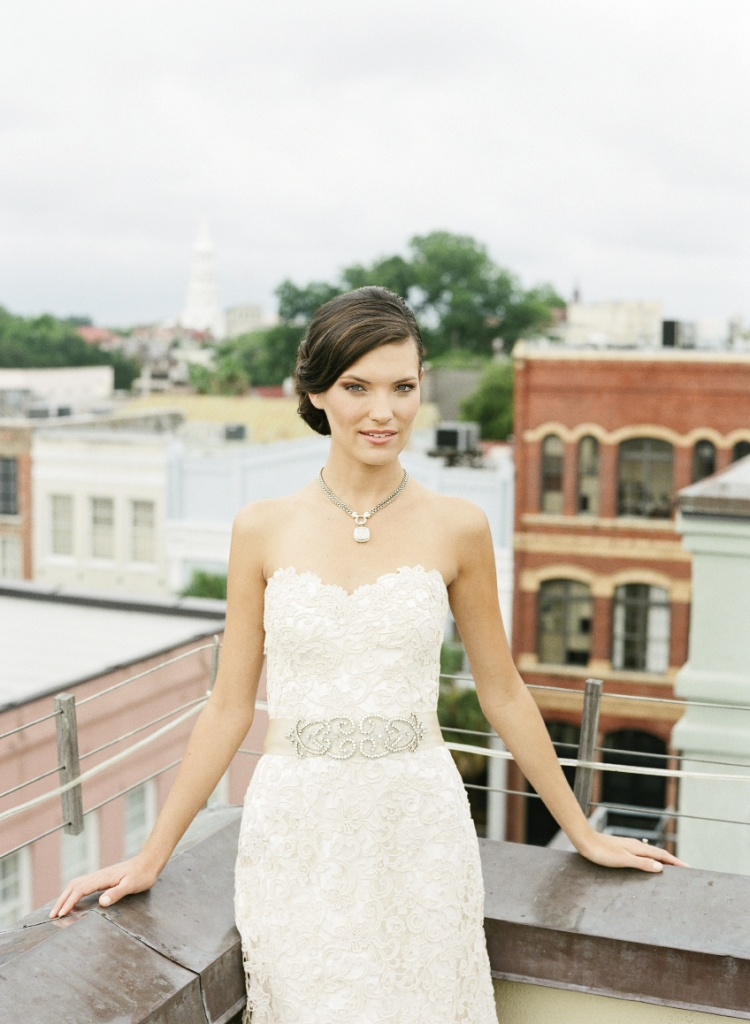 "Modern Trousseau's ""Scout"" strapless guipure lace and satin fit-and-flare gown. LOVE's cream satin sash with crystal embellishments from Gown Boutique of Charleston. David  Yurman's sterling silver and pavé diamond pendant and wheat chain necklace from his Albion collection at REEDS  Jewelers. Yellow gold and diamond ring from Joint Venture Estate Jewelers. Image by Corbin Gurkin, photographed at The Vendue."