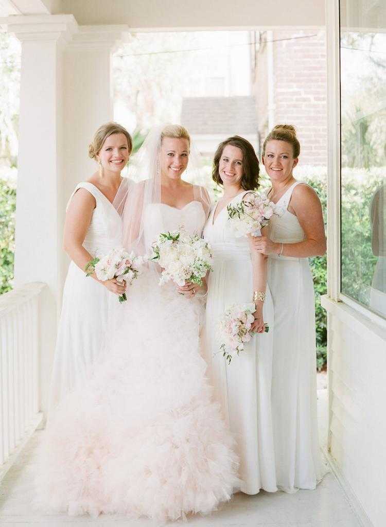 Bride's gown by Monique Lhuillier, available in Charleston through Maddison Row. Earrings by Ippolita, available in Charleston through REEDS Jewelers. Bridal styling by Lindsey Nowak and Cacky's Bride + Aid. Bridesmaids' attire by Monique Lhuillier from Bella Bridesmaids. Florals by Gathering Floral + Event Design. Hair and makeup by Ashley Brook Perryman. Photograph by Corbin Gurkin.