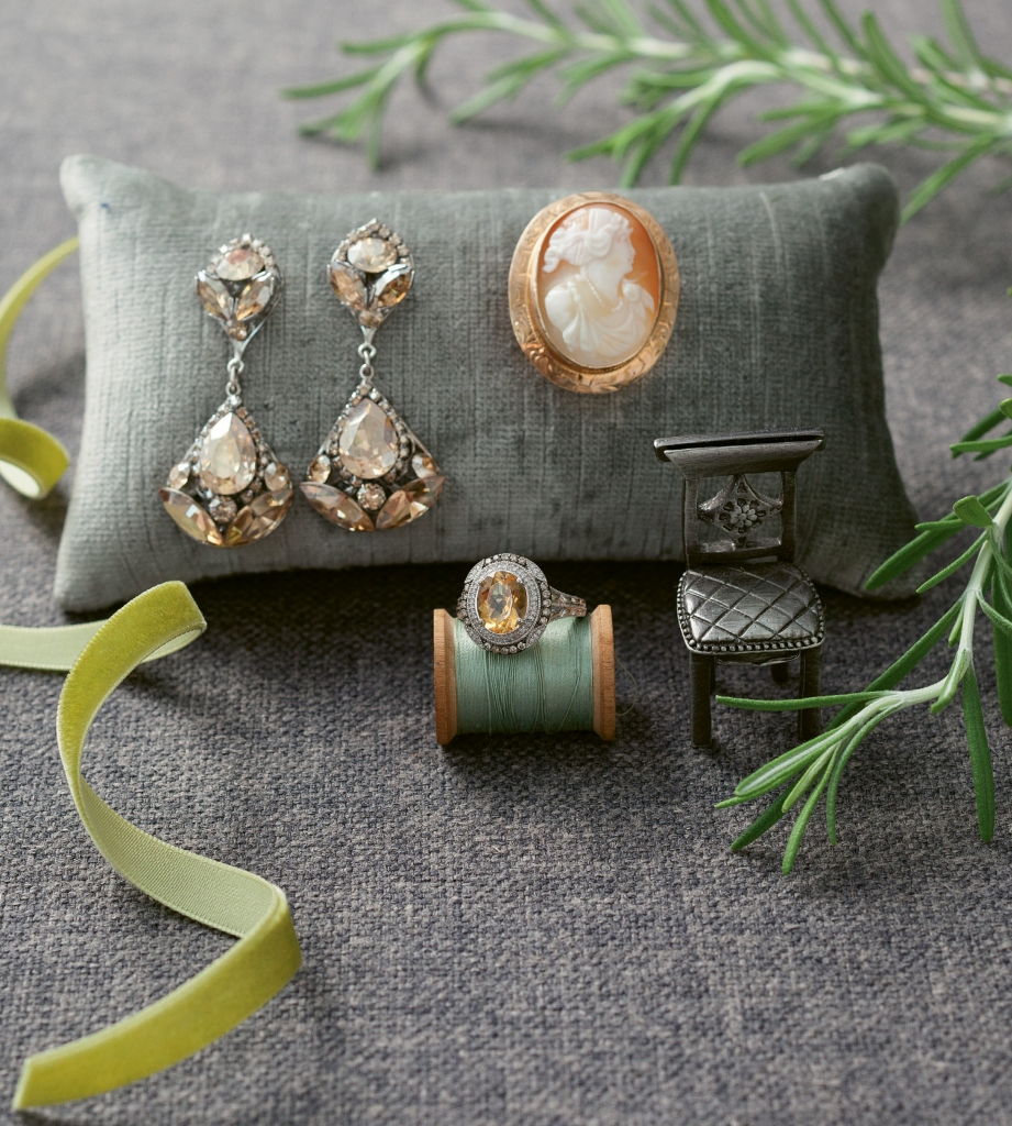 "(clockwise from left) Sara Gabriel's ""Jasmine"" earrings from Maddison Row. Antique cameo brooch from Croghan's Jewel Box. Sterling silver, citrine, and diamond ring from REEDS Jewelers. Ribbon from May Arts. Fabric from GDC Home. Pillow from Croghan's Jewel Box.  Photography by Gayle Brooker"