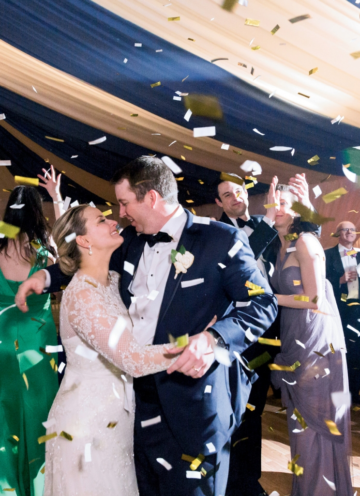 """Skip and I had a rule that we would take breaks every so often to hold hands and savor the details together,"" Laura explains. Exhibit A: this stolen moment just as the confetti cannon exploded. (Photo by Corbin Gurkin)"