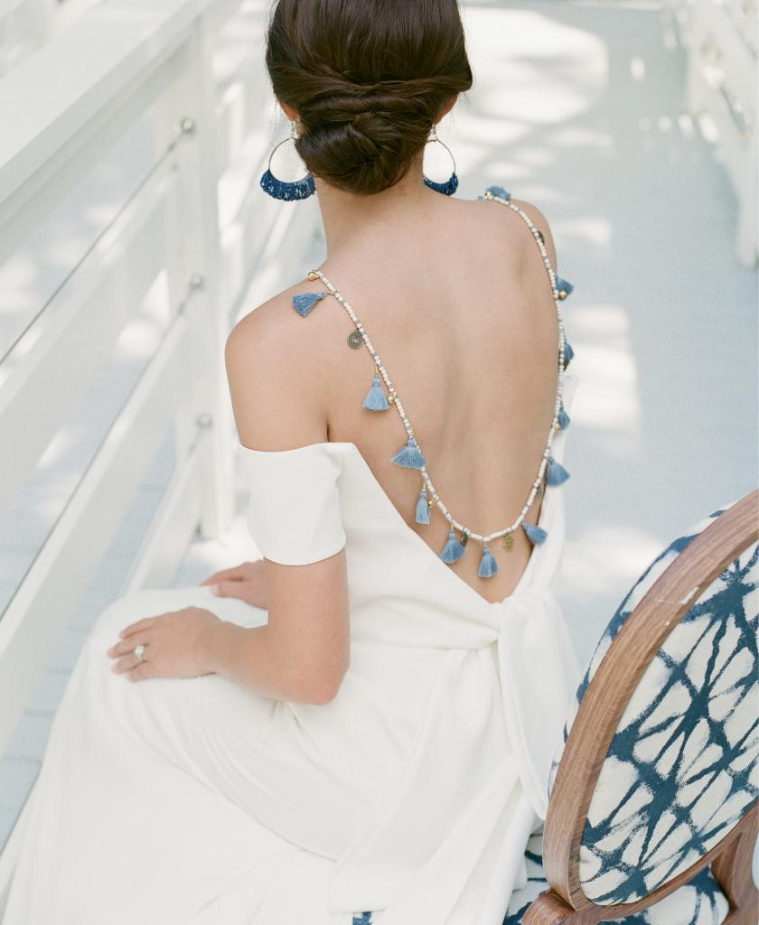 "Lela Rose's ""The Capri"" off-shoulder gown from Maddison Row South. Lapis beaded earrings and Balinese tassel necklace, both from Celadon Home. C. Gonshor's diamond and platinum ring from Diamonds Direct. Chair from Ooh! Events"