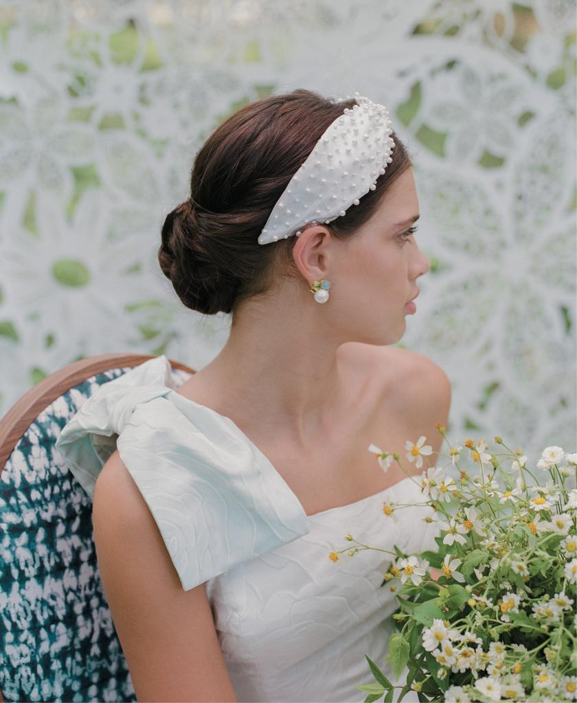 """The Reims"" gown (with detachable blue shoulder bow) from Emily Kotarski Bridal. Mazza's earrings from Croghan's Jewel Box. ""Posh"" headband from Untamed Petals. Flowers grown by One Wild Acre. Lace Tyvek backdrop from Laser Cutting Shapes. Chair from Ooh! Events"