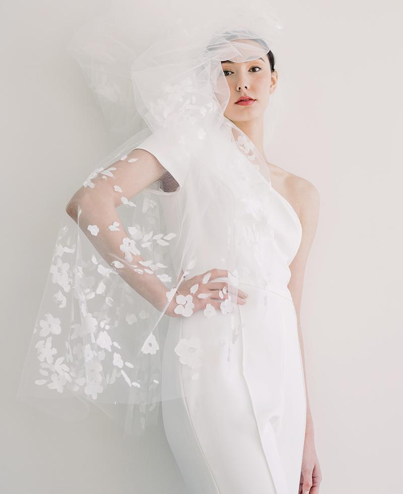 "Amsale Nouvelle's one-shoulder crepe jumpsuit from Maddison Row South. Katherine McDonald's ""Riverland"" hand-painted veil (shown gathered) from Kate McDonald Bridal"