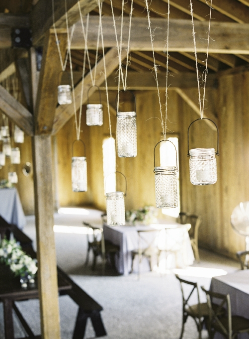 "UP IN THE AIR: Event designers Kristin and Heather tucked candles into hobnail jars, then used twine to hang the vessels at varying heights from the Cotton Dock's ceiling beams. ""The décor was simple, but fit us perfectly,"" says Marianna."