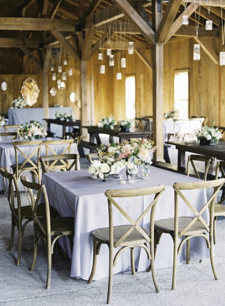 "WOODWORKS: Silver-gray linens and pale, unfinished wooden chairs from Snyder Events kept the reception room light overall, while Snyder's dark-stained farm tables added depth to the design. ""Marianna wanted a look that felt like things had been collected from someone's own home,"" Heather says of the bride's aesthetic. A mix of vessels from Heather's collection—including an antique pewter teapot—and varying floral  arrangements did just  the trick."