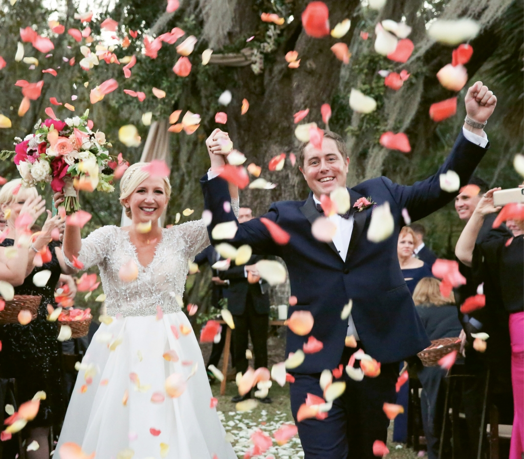 Emily Harkins and Christopher Christensen beamed through a shower of confetti-colored rose petals after being pronounced husband and wife at the Legare Waring House.  <i>Photograph Jennifer Bearden</i>