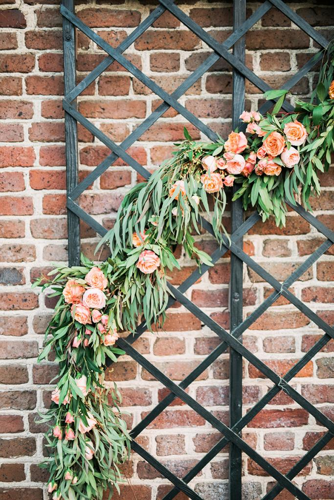 A snaking garland of peach roses and leafy greens woven into the trellis in the restaurant's courtyard imparts a clever idea: Set up a floral installation like this for your ceremony backdrop, then let it serve as a selfie station during your the reception.