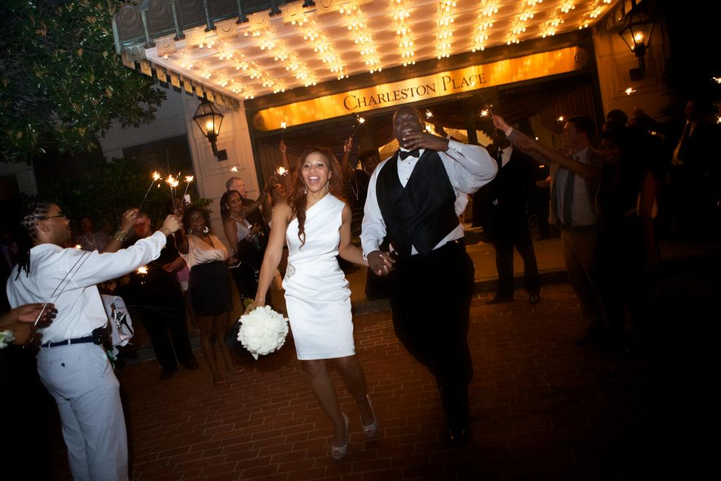 "SURROUNDED BY LOVE: Dressed in a little white getaway dress, Richelle and Cedric exit to a tunnel of sparklers. ""We are blessed to have each other and to have family, friends and coworkers who love us dearly!"" says Richelle."