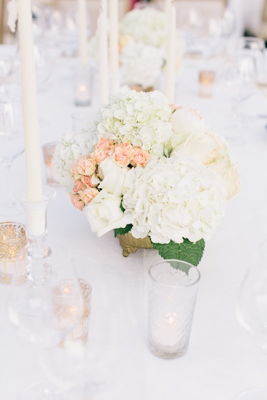 Harkening colors from invitation suite and the hand-held bouquets, arrangements of leafy white hydrangeas, white roses, and pale pink spray roses dotted the dining tables.