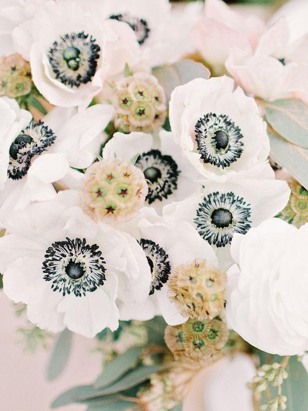 Arranged by the bride and her gals, arrangements of black-and-white anemones, scabiosa pods, and seeded eucalyptus sprang from simple glass vases.