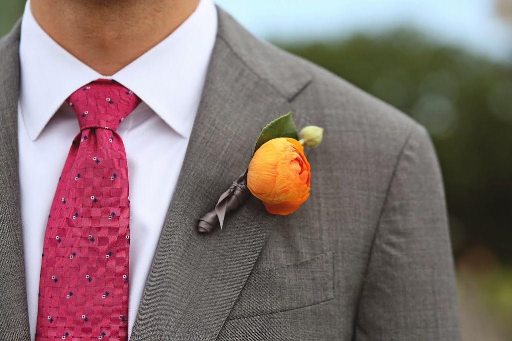 DAPPER DUDE: Engaging Events' Judy Johnston polished off the groom's handsome orange sherbet-hued ranunculus boutonniere with grey satin ribbon.