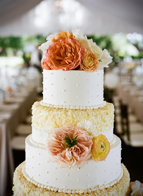 DRESSED TO IMPRESS: Bright ranunculus and cabbage roses accented the four-tiered, textured confection by Fish Restaurant.