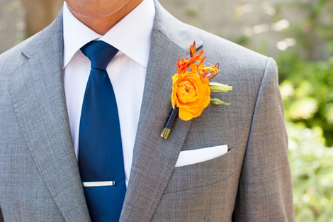 FINISHING TOUCH: The groom's papaya-hued boutonnière popped against his gray suit, and the navy blue tie echoed the hue of the bridesmaid frocks.