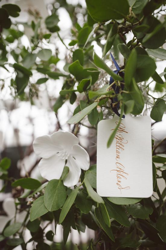 GOLDEN TICKET: Escort cards were printed with gold ink to tie in the gold foil found throughout the rest of the event's paper goods. The porcelain flowers that were wired to the trees were given out as favors.