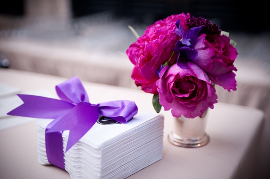 DRAMATIC DETAIL: Bright purple ribbon used to tie off a simple stack of napkins provided another burst of color that reinforced the wedding's palette.