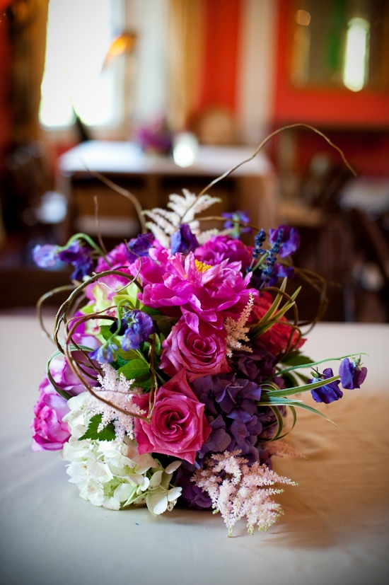 "CONTROLLED CHAOS: Wild arrangements in bold colors added an ""enchanted forest"" feel to the vintage-glam reception."