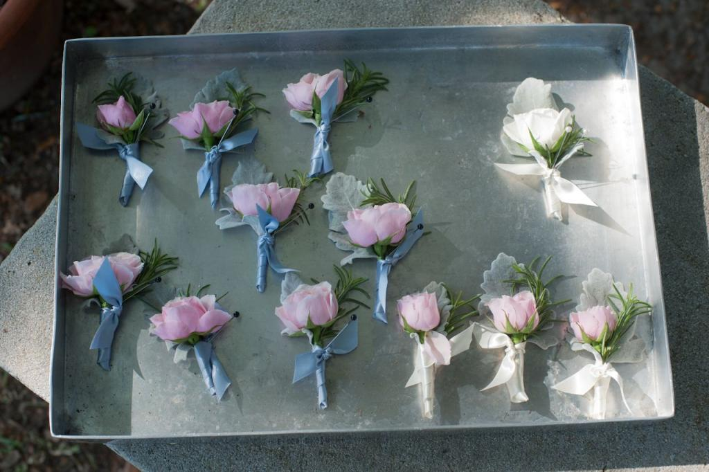 SPRING HUES: Groomsmen wore pink rose boutonnieres accented with rosemary lamb's ear. Patrick stood out from the bunch with a white rose variation.