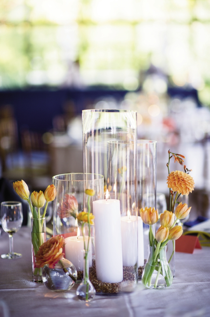 CENTER OF ATTENTION: Blooms with varying textures and shapes in shades ranging from orange to peach accented simple clear glass hurricane vases to form sophisticated centerpieces.
