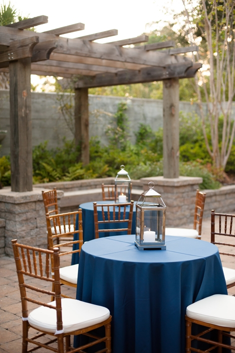THE TABLES ARE SET: Deep gold Chiavari chairs and round cocktail tables draped in navy linens from Snyder Event Rentals offered patio seating in keeping with the wedding's rich palette.