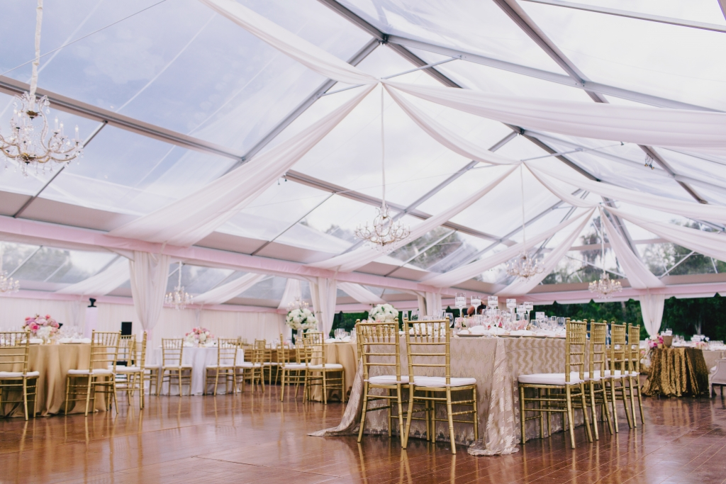 A clear-top tent with minimal draping provided shelter while preserving the alfresco feel of the reception. <i>Photograph by Hyer Images</i>