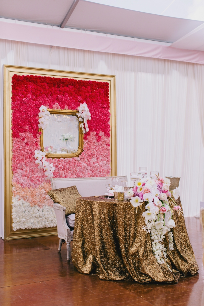 """We took every great idea we could come up with—sequin linens, cascading florals, vintage  seating—then backed it with a 10,000-stem, eight-foot ombré flower wall in a custom-built frame,"" says Luke of the sweetheart table. The finishing touch? A mirror with the couple's monogram. <i>Photograph by Hyer Images</i>"