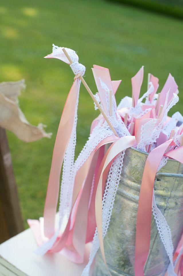 A WHIMSICAL TOUCH: Before taking their seats, guests picked up one of the bride's handmade contributions—wishing wands made of pink and white ribbons to wave as the newlyweds walked together up the aisle.
