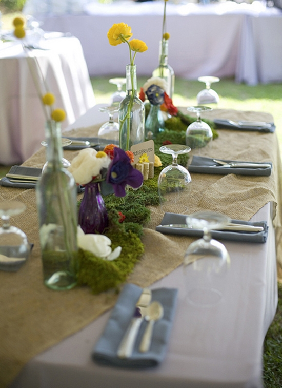 DINING OUT: Burlap table linens, repurposed wine bottles, wildflowers, and colorful vases gave the reception spreads a cheerful, earthy feel.