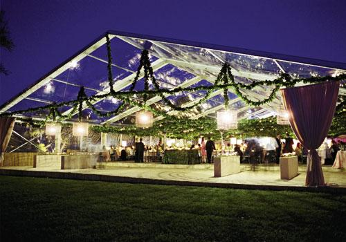 Pavilion Perfection:The dining hall was lined with rye grass planters sprouting with copper garden signs engraved with guest names and table numbers. The enormous metal drum shades were four feet in diameter and four feet tall.
